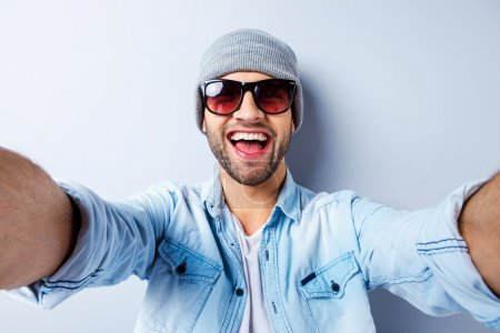 Photo for Top view of handsome young man in hat and sunglasses making selfie and smiling - Royalty Free Image