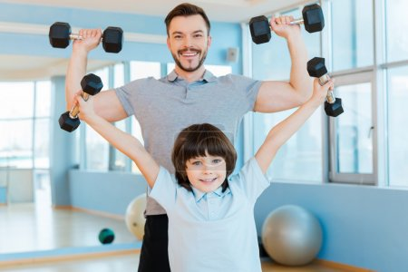 Father and son exercising with dumbbells
