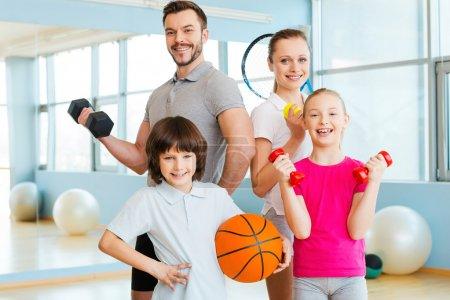 Family holding different sports equipment