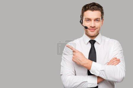 Foto de Apuesto joven en ropa formal y auriculares mirando a la cámara y señalando lejos mientras está de pie contra fondo gris - Imagen libre de derechos