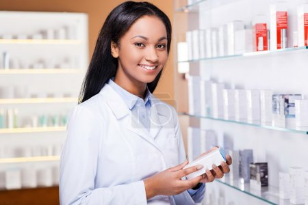 African woman in lab coat in drugstore