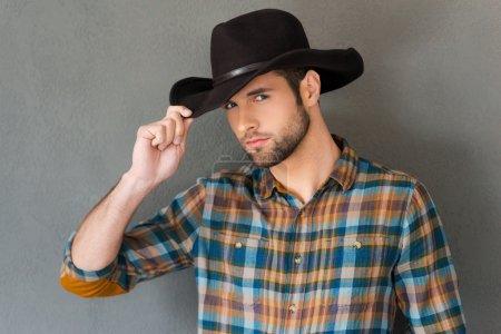 Photo pour Jeune homme beau ajustant son chapeau de cowboy et regardant l'appareil-photo tout en restant contre le fond gris - image libre de droit