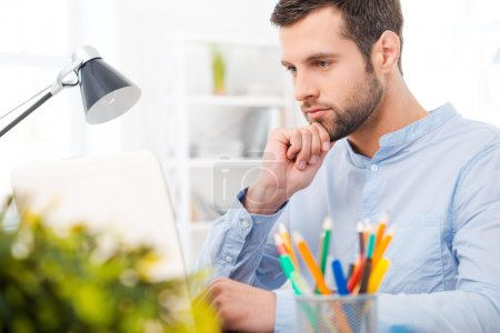 Photo for Handsome young man in shirt working on laptop and holding hand on chin while sitting at his working place - Royalty Free Image