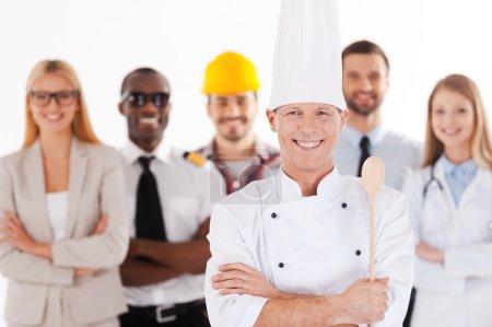 Photo pour Chef masculin confiant en uniforme gardant les bras croisés et souriant tandis que le groupe de personnes dans différentes professions debout en arrière-plan - image libre de droit