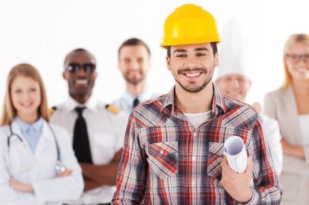 Photo pour Jeune homme confiant en casque de sécurité tenant le plan et souriant tandis que le groupe de personnes dans différentes professions debout en arrière-plan - image libre de droit