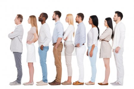Photo for Standing in a row. Full length of confident multi-ethnic group of people in smart casual wear looking away while standing in a row and against white background - Royalty Free Image
