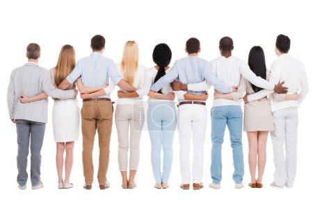 Photo pour Vue arrière pleine longueur du groupe de personnes diverses collant les uns aux autres tout en se tenant debout sur fond blanc - image libre de droit