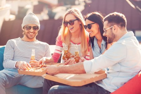 Photo for Four young cheerful people eating pizza and drinking beer while sitting at the bean bags on the roof of the building - Royalty Free Image