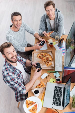 Men playing computer games and eating pizza