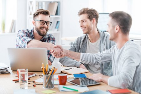 Photo for Business people shaking hands while sitting at the desk in office - Royalty Free Image