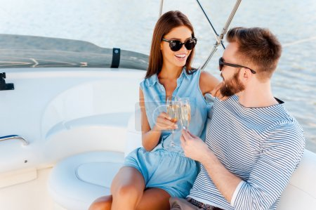 Couple holding glasses with champagne on yacht
