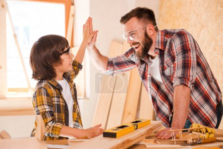 carpenter and son giving high-five