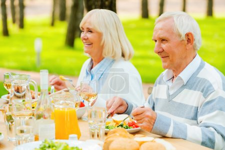 Photo for Senior couple enjoying meal together while sitting at the dining table outdoors - Royalty Free Image
