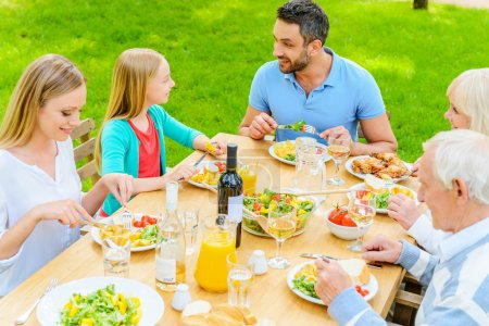 family enjoying meal outdoors