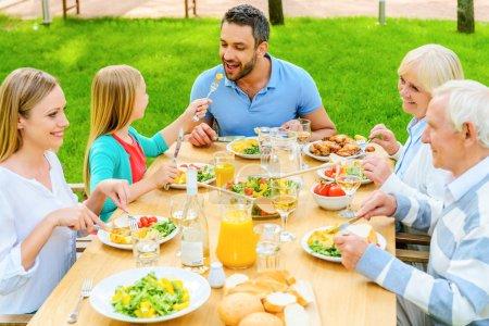 happy family enjoying meal outdoors