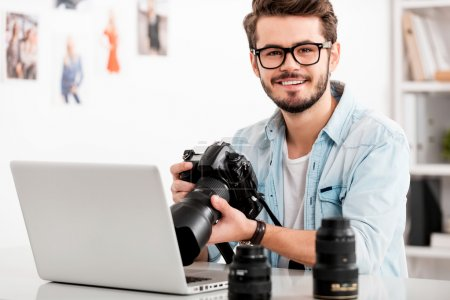 Happy young man holding camera