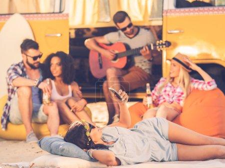 woman lying near minivan with friends