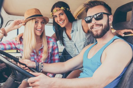 women and man sitting inside of minivan
