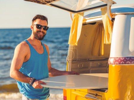 Photo pour Souriant jeune homme prenant skimboard de coffre de voiture et souriant à la caméra en se tenant debout sur la plage - image libre de droit