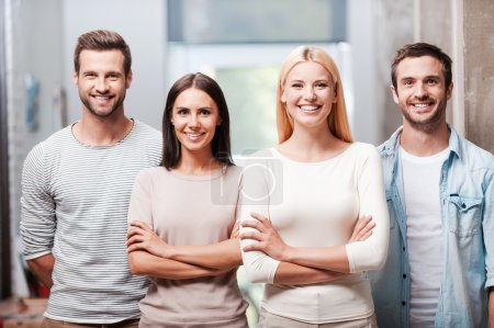Photo for Four young business people in smart casual wear standing close to each other and smiling discussing - Royalty Free Image