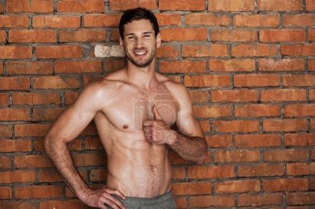 Foto de Joven alegre hombre sin camisa sosteniendo el pulgar hacia arriba y sonriendo mientras está de pie contra la pared de ladrillo - Imagen libre de derechos