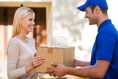 Photo for Side view of happy young delivery man giving a cardboard box to young woman while standing in front of the house - Royalty Free Image