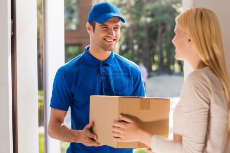 delivery man giving cardboard box to woman