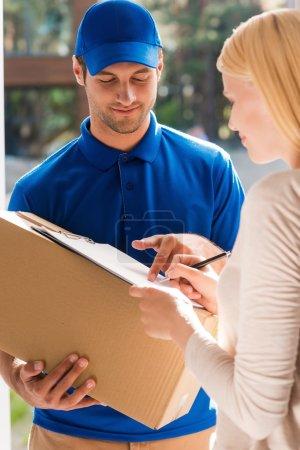 Photo pour Signez ici. Beau jeune livreur tenant une boîte en carton tandis que belle jeune femme mettant la signature dans le presse-papiers - image libre de droit
