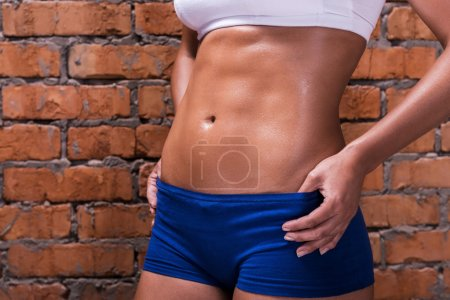 Photo for Close-up of beautiful young woman with flat abs holding hands on hip while standing against brick wall - Royalty Free Image