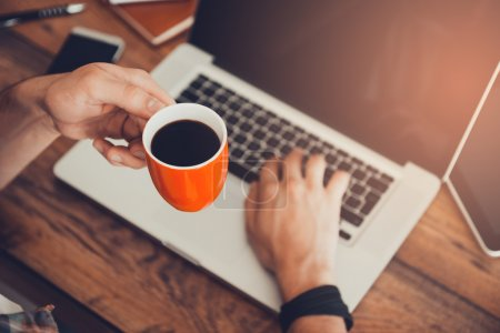 man working on laptop and holding cup