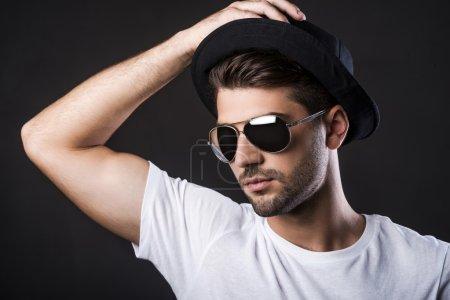 young man adjusting his hat