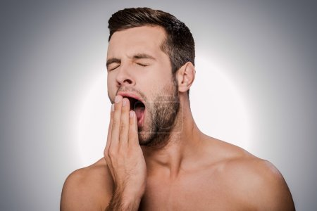 man covering mouth by hand and yawning