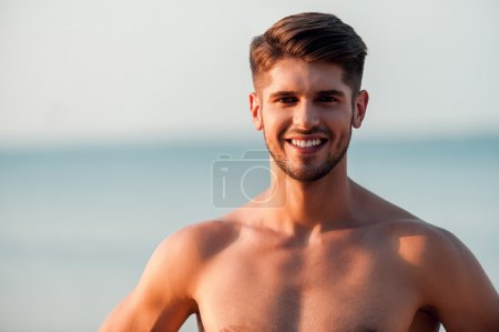 Happy young muscular man looking at camera and smi...