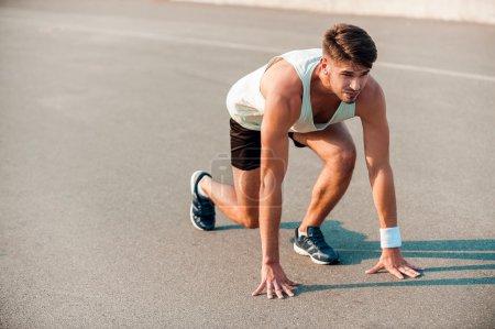 Muscular man standing in starting line