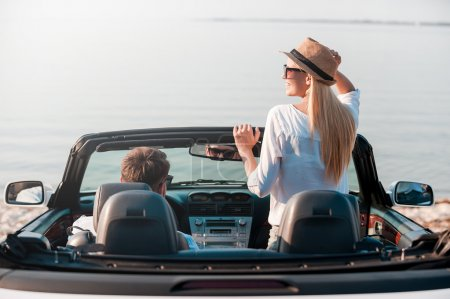 woman and her  boyfriend enjoying scenery in convertible