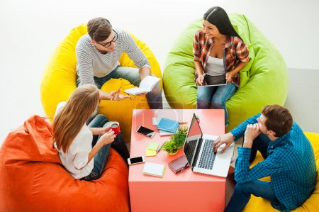 Photo pour Vue du dessus de quatre jeunes gens travaillant ensemble tout en étant assis aux sacs de haricots colorés - image libre de droit