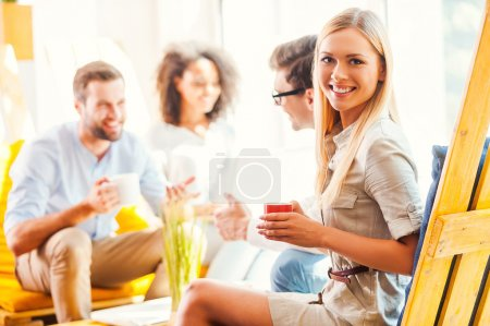 Photo for Happy young woman holding cup of coffee and looking at camera while her colleagues discussing something in the background - Royalty Free Image