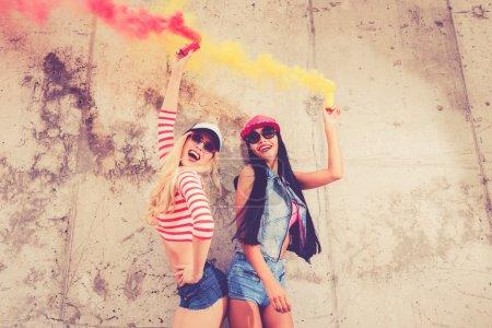 women holding smoke bombs