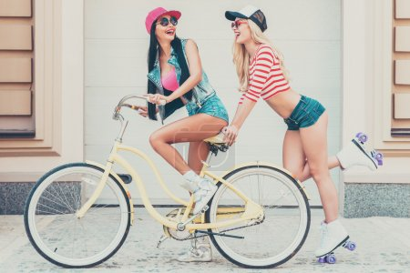 Woman riding on bicycle with friend skating