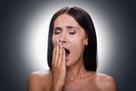 woman covering mouth by hand and yawning