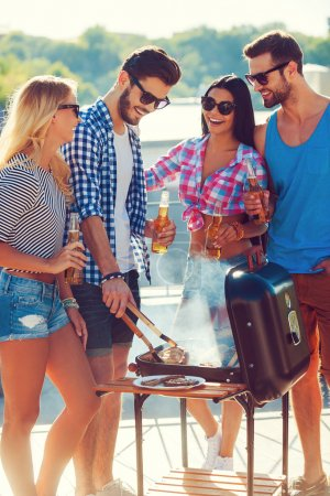 people barbecuing while standing on the roof