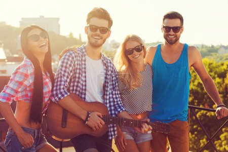 Photo for Group of happy young people bonding to each other and looking at camera while standing on the roof with guitar - Royalty Free Image