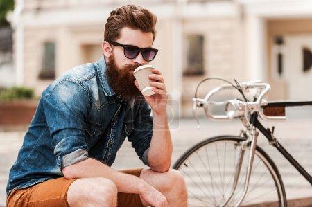 Photo pour Barbu de beau jeune homme de boire du café en plein air - image libre de droit