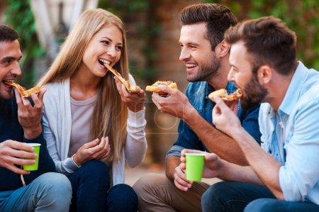 froehliche junge menschen essen pizza