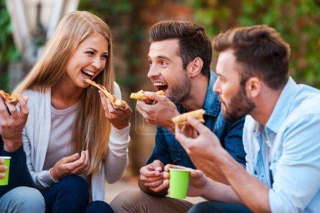 verspielte junge menschen essen pizza