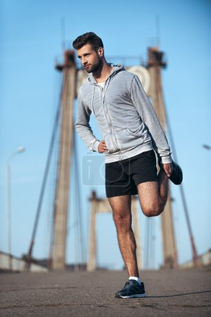 Photo for Full length of confident young man doing stretching exercises before running while standing on the bridge - Royalty Free Image