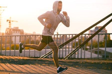 confident man running along the bridge