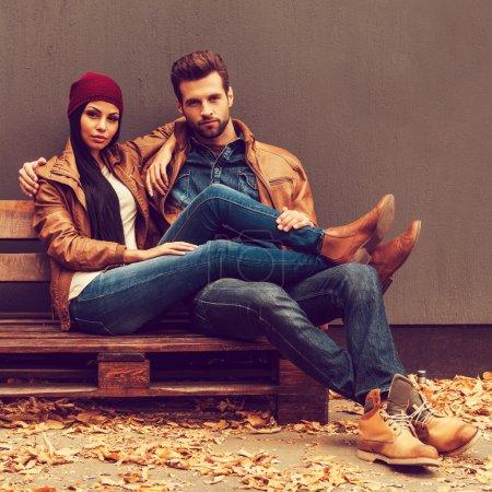 Photo pour Beau jeune couple collant les uns aux autres tout en étant assis sur la palette en bois avec un mur gris en arrière-plan et des feuilles tombées allongées sur le sol - image libre de droit