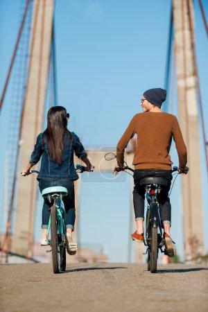 Photo pour Vue arrière du beau jeune couple riding bicyclettes le long du pont et en regardant l'autre - image libre de droit