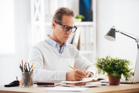mature man writing something in his notebook